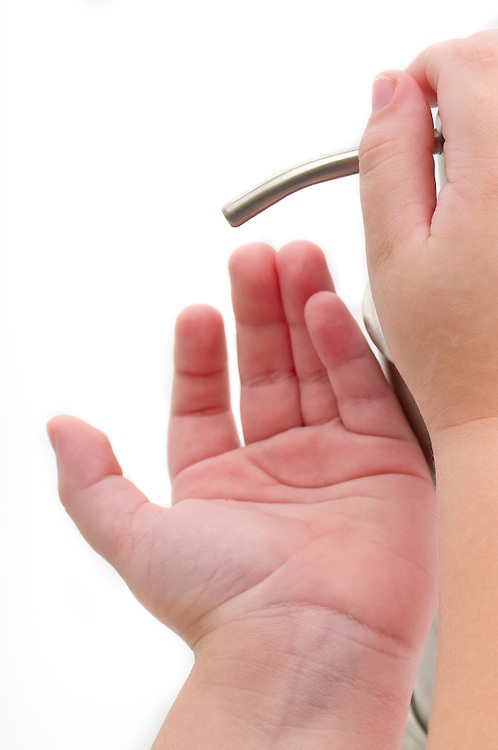 Close up of hand sanitizer being poured into child hands. Isolated on white.