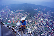 Cheng-Yuan Cheng, a maintainence worker changes lightbulbs near the dizzying top of Taipei 101, the world's tallest building.