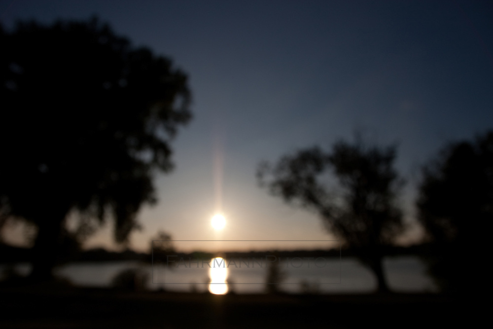 The sun sets over Lake Nokomis on a clear sky evening in summer