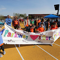 Students from Parkway Elementary carry their banner around the track as part of the opening ceremonies for Wednesday's Special Olympics held at Tupelo High School.
