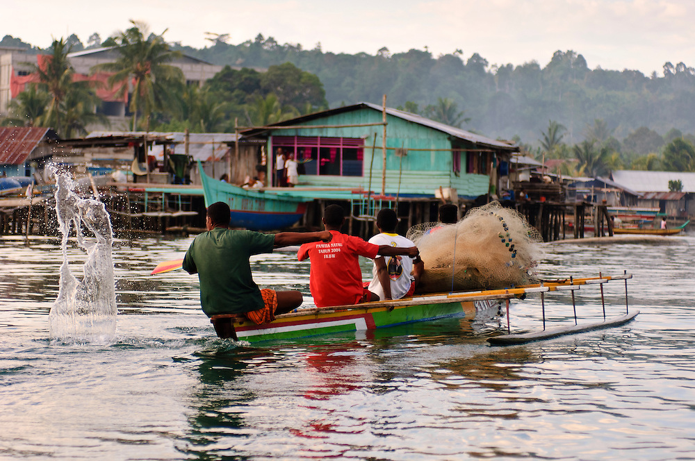 Fishermen in a dugout canoe with an outrigger, Manokwari, West Papua, Indonesia. Manokwari is a small town on the north east coast of the Bird's Head Peninsula, West Papua, Indonesia.  Its harbour has many wrecks from WWII.