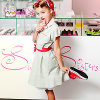 Female child standing on one leg dressed in 1950's clothing wearing red sneakers and head scarf licking lolly in sweet shop looking at camera