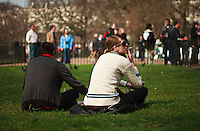 A man and woman listen at Speaker's Corner in Hyde Park, London, England.