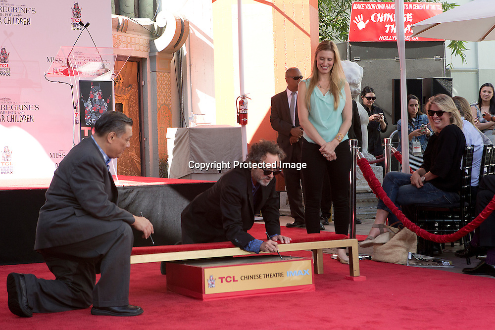 Film director, writer and producer Tim Burton signing his name in the cement block during the hand and foot print ceremony Thursday afternoon in the TLC Chinese Theatre in Hollywood