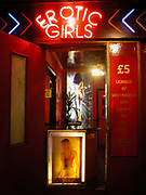 Erotic Girls neon sign above the doorway of a strip joint licensed by Westminster City Council, London, 2000's
