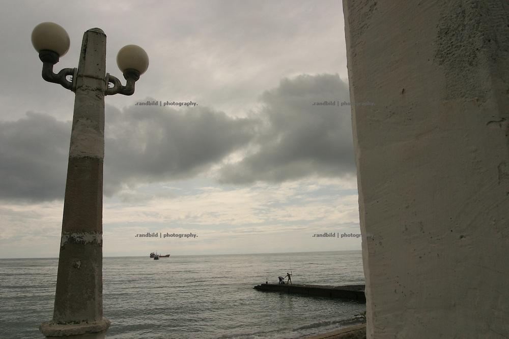 Georgien/Abchasien, Suchumi, 2006-09-02, Zwei Angler im Regen auf einer Pier in Suchumi. Abchasien erklärte sich 1992 unabhängig von Georgien. Nach einem einjährigen blutigen Krieg zwischen den Abchasen und Georgiern besteht seit 1994 ein brüchiger Waffenstillstand, der von einer UNO-Beobachtermission unter personeller Beteiligung Deutschlands überwacht wird. Trotzdem gibt es, vor allem im Kodorital immer wieder bewaffnete Auseinandersetzungen zwischen den Armee der Länder sowie irregulären Kämpfern.  (Two fischermen in the rain on a pier in Sokhumi. Abkhazia declared itself independent from Georgia in 1992. After a bloody civil war a UNO mission observing the ceasefire line between Georgia and Abkhazia since 1994. Nevertheless nearly every day armed incidents take place in the Kodori gorge between the both armys and unregular fighters )