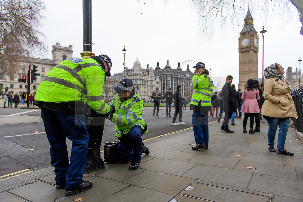 © Licensed to London News Pictures. 31/12/2016. London, UK. Police officers carry out security checks on lamp posts around Parliament Square in Westminster, London ahead of tonight's New Year celebrations. Security surrounding this year's event has been heightened following a terrorist attack at a Christmas market in Berlin earlier this month. Photo credit: Ben Cawthra/LNP