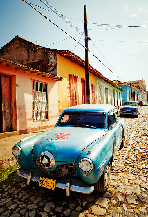 A pair of vintage cars parked on a colorful street in Trinidad, Cuba.<br /> <br /> + ART PRINTS +<br /> To order prints or cards of this image, visit:<br /> http://greg-stechishin.artistwebsites.com/featured/vintage-cuba-2-greg-stechishin.html