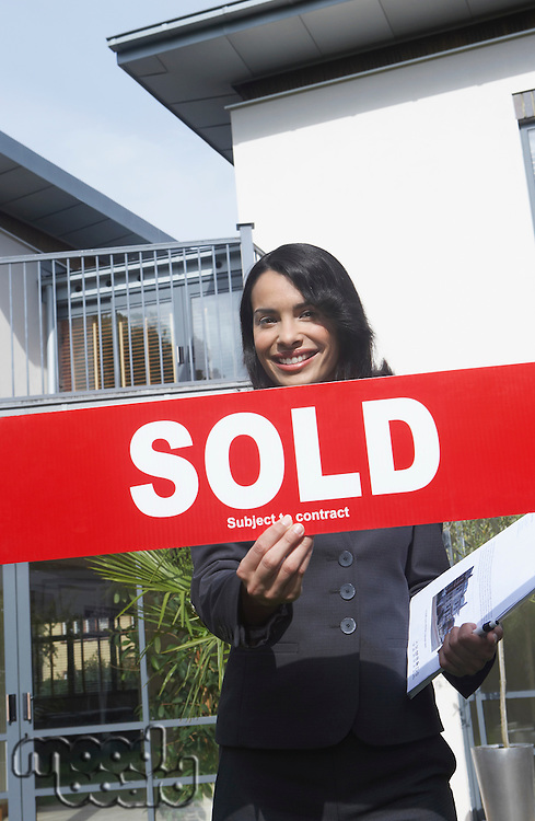 Real estate agent holding sold sign outside house portrait