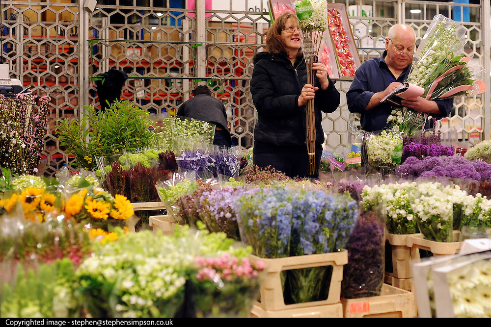 © Licensed to London News Pictures. 15/03/2012. London, UK. A woman buys her flowers from a wholesaler. The Mothering Sunday sales rush is on for flower growers, suppliers, florists and retailers amongst the Flowers at the New Covent Garden Flower Market on March 15th 2012 in London, England. New Covent Garden Flower Market is London's premier wholesale market stocking the widest range of flowers, plants and foliage in the UK. The run up to Mothers' Day is crucial in the flower selling calendar as Mothers' Day sales are condensed into about four days making the market very busy. Traditionally, Mothering Sunday was a day when children, mainly daughters, who had gone to work as domestic servants, were given a day off to visit their mother and family. Today, Mother's Day is a time when children give flowers and cards to their mothers, and generally pamper them..  Photo credit : Stephen SImpson/LNP