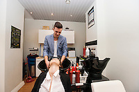 Male hairstylist washing female customer's hair in beauty salon