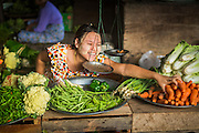06 JUNE 2014 - IRRAWADDY DELTA,  AYEYARWADY REGION, MYANMAR: A woman sells carrots in the market in Pantanaw, a town in the Irrawaddy Delta (or Ayeyarwady Delta) in Myanmar. The region is Myanmar's largest rice producer, so its infrastructure of road transportation has been greatly developed during the 1990s and 2000s. Two thirds of the total arable land is under rice cultivation with a yield of about 2,000-2,500 kg per hectare. FIshing and aquaculture are also important economically. Because of the number of rivers and canals that crisscross the Delta, steamship service is widely available.   PHOTO BY JACK KURTZ