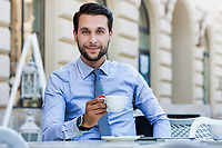 Portrait of young attractive businessman sitting in cafe while drinking coffee
