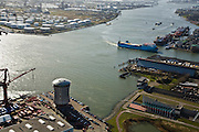 Nederland, Zuid-Holland, Schiedam, 04-03-2008; Nieuwe Maas met links het cilindrische hoofdkantoor van de Mammoet-van Seumeren Group (Groep), rechtsonder de ingang van de Beneluxtunnel, een coaster van de Norfolk Line vaart de Vulcaanhaven binnen,  aan de overzijde van de rivier olieraffinaderij Pernis; . .luchtfoto (toeslag); aerial photo (additional fee required); .foto Siebe Swart / photo Siebe Swart