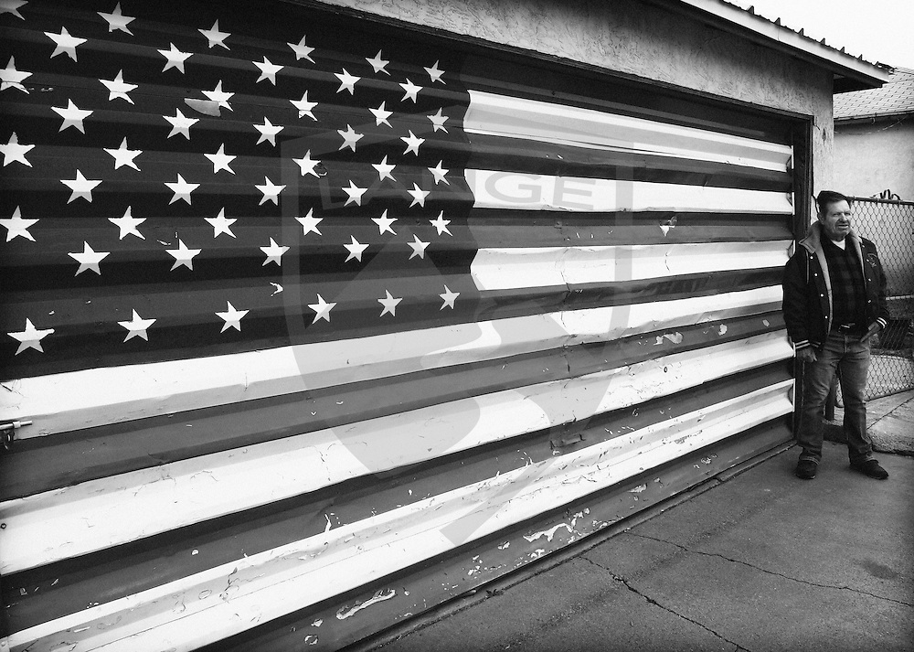 a man stands with pride and patriotism in front of the american flag that he painted on his garage door.  asked why he did it, he indicated that he was proud to be an american.  suburban albuquerque, new mexico, usa