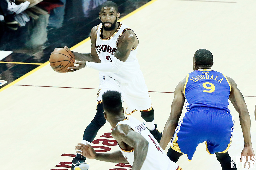 07 June 2017: Cleveland Cavaliers guard Kyrie Irving (2) passes the ball over Cleveland Cavaliers guard Iman Shumpert (4) over Golden State Warriors forward Andre Iguodala (9) during the Golden State Warriors 118-113 victory over the Cleveland Cavaliers, in game 3 of the 2017 NBA Finals, at  the Quicken Loans Arena, Cleveland, Ohio, USA.