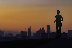 Primrose Hill, London, October 4th 2016. A woman takes an early morning run as dawn breaks across London, throwing the city's skyline into silhouette.