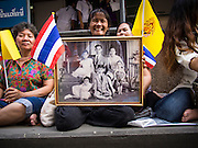 01 AUGUST 2013 - BANGKOK, THAILAND: A woman holds up a picture of Bhumibol Adulyadej, the King of Thailand, and his family, in front of Siriraj Hospital, before the King left the hospital Thursday. The King, 85, was discharged from Bangkok's Siriraj Hospital, where he has lived since September 2009. He traveled to his residence in the seaside town of Hua Hin, about two hours drive south of Bangkok, with his wife, 80-year-old Queen Sirikit, who has also been treated in the hospital for a year.      PHOTO BY JACK KURTZ