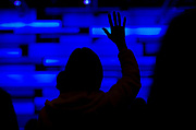 A congregant raises her hands in prayer during service at Door Creek Church in Cottage Grove, Wisconsin, Sunday, Feb. 4, 2018.