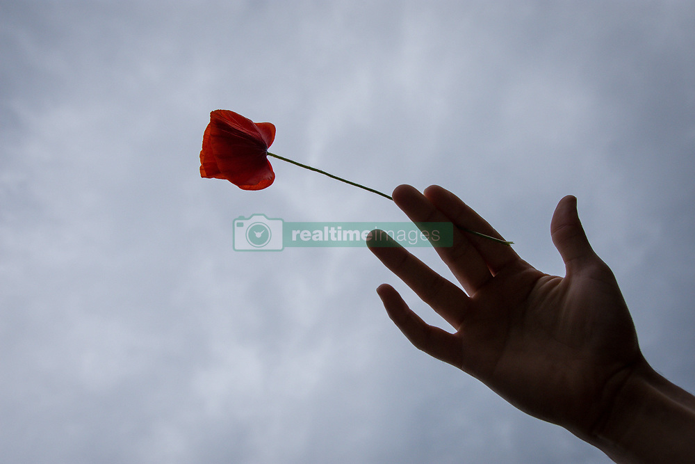 May 1, 2019 - Chania, Greece - A hand seen with a red flower during the protest. .Demonstration took place in many regions in Greece demanding better salary and worker's rights. In May 1886, the labour unions in Chicago were rallied by claiming working hours at 8 hours and better working conditions. (Credit Image: © Nikolas Joao Kokovlis/SOPA Images via ZUMA Wire)
