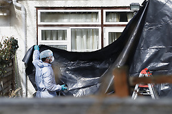 © Licensed to London News Pictures. 14/03/2018. London, UK. Police IN protective clothing cover windows at the rear of the house of Russian exile Nikolai Glushkov in south west London. Mr Glushkov, a friend of oligarch Boris Berezovsky, and a former deputy director of Russian state airline Aeroflot, died at his home in Monday night. Police continue to investigate. Photo credit: Peter Macdiarmid/LNP
