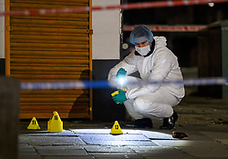© Licensed to London News Pictures. 20/08/2018. London, UK. Police forensics examines a bullet casing, at the scene of a shooting on Kingsbury Road in North London in which three people have been shot. No arrests have been made after emergency services rushed to the scene on Kingsbury High Road in Brent at 9.45pm. Photo credit: Ben Cawthra/LNP