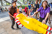 31 MAY 2014 - BANGKOK, THAILAND:  Workers at a McDonald's restaurant in Bangkok take away Ronald McDonald because they were afraid the fast food icon would attract protestors opposed to the military coup. Some McDonald's restaurants in Thailand have become gathering places for anti-coup protestors. The restaurant chain has taken out ads trying to discourage people from protesting in and around the restaurants and put up signs asking people not to protest in the restaurant. Bangkok was mostly quiet Saturday. There were only a few isolated protests against the coup and military government.    PHOTO BY JACK KURTZ