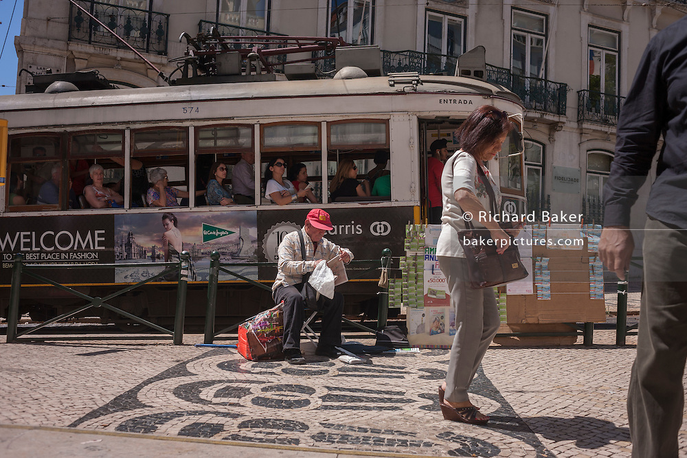 A traditional Lisbon tram passes pedestrians at Baixa Metro station near Praca Luis de Camoes, in the Chiado district of the city.