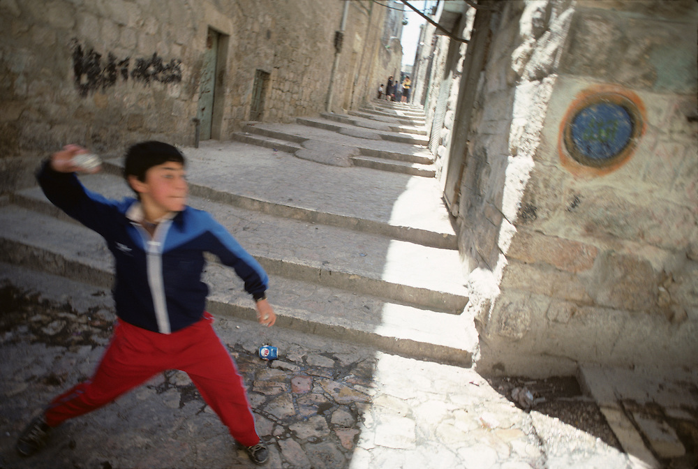Israel, Jerusalem, Portrait Palestinian boy throwing rock in streets of Arab Quarter