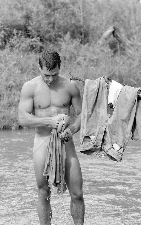nude man with wet clothes in a stream
