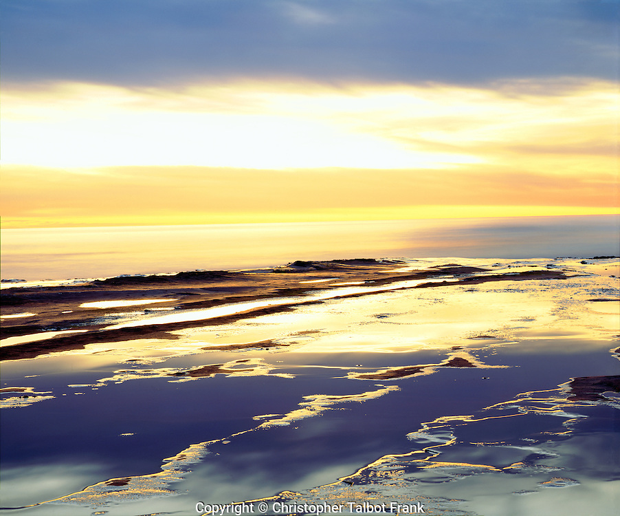 I went down to the Pacific Ocean coastline to take this amazing abstract tide pool sunset photo.  This bright yellow and dark gray cloud reflected in the coastal sandstone rock patterns.