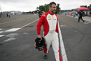 Jason Harper walks from the garage to the start for his qualifying session at the Ferrari Challenge North America in Watkins Glen, New York, USA, on Saturday, September 20, 2014. Photographer: Mike Bradley/Bloomberg