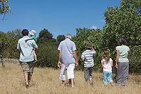 Three-generation family with three children (3-11) walking in field back view