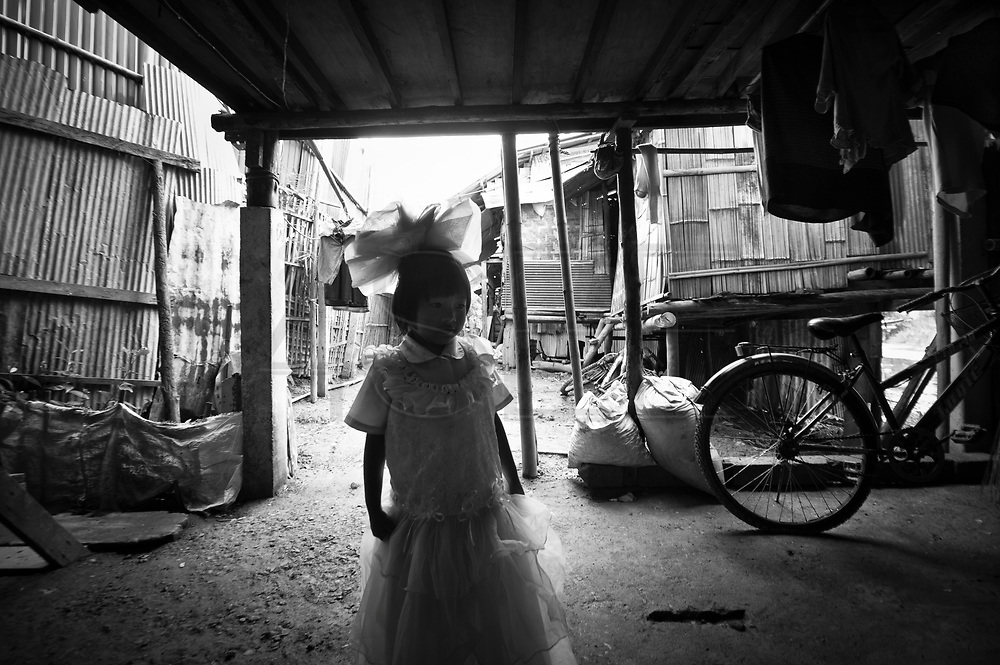 A young girl playing princess in the Lahu slum. In a rather poor neighborhood, this is not a common sight.??On the banks of a polluted river, in poorly-built houses, live more than a hundred people from the Lahu tribe. They live in a slum in Chiang Mai, Thailand, away from the Lahu people?s original way of life. Usually, the Lahu people get their resources from the forest. The slum has been there for decades.