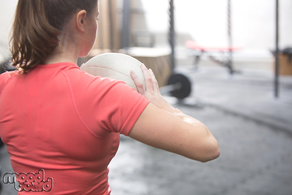 Rear view of woman holding medicine ball in crossfit gym
