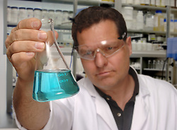 Chemist holding erlenmeyer flask containing blue chemical