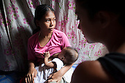 UK celebrity Myleene Klass weeps with Vilma Tacuyo, 20, while Vilma breastfeeds her youngest child, Ulderico (10 months), in their one room home in an urban slum in Paranaque City, Metro Manila, The Philippines on 18 January 2013. Vilma had raised her first 3 children on formula and had to cut down on food for her family to afford it. Both John Ashley, 4, and Justin, 3, are malnourished and stunted, and after losing one of her children, she now breastfeeds her youngest, Ulderico. Photo by Suzanne Lee for Save the Children UK
