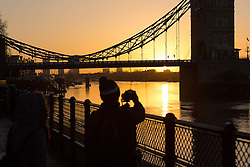 © Licensed to London News Pictures. 02/01/2017. LONDON, UK.  Tourists photograph a golden sunrise behind Tower Bridge on the River Thames in London this morning during cold and clear weather following heavy rain yesterday.  Photo credit: Vickie Flores/LNP