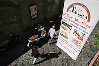 "NAPLES, ITALY - 10 OCTOBER 2018:  banner of La Taverna a Santa Chiara hangs from its balcony here in the historical center of Naples, Italy, on October 10th 2018.<br /> <br /> The idea of the founders Nives Monda and Potito Izzo (two really unusual names in southern Italy) was to create a ""taste gate"" of Campania products. La Taverna a Santa Chiara, founded in 2013, is a modern tavern whose strengths are the choice of regional and seasonal products and mostly small producers. Small restaurant, small producers.<br /> The two partners tried to put producers and consumers in direct contact, skipping the distribution, and managing to reduce the costs of the products considerably. Nives and Potito managed to create a simple kitchen, at moderate costs but with high quality raw materials.<br /> ""A different restaurant idea,"" says Nives, ""the producers deliver their products at low prices and the tavern manages to make traditional dishes with niche products"".<br /> Nives Monda has been a labor consultant for 20 years. Potito Izzo is the chef who has always been loyal to the  family cuisine. When he embraced the idea of Nives he found in the tavern the natural place to express the tradition of Neapolitan cuisine. Nives defines him as a ""comfort food chef"". Their partnership is a true friendship that has lasted for over 10 years."