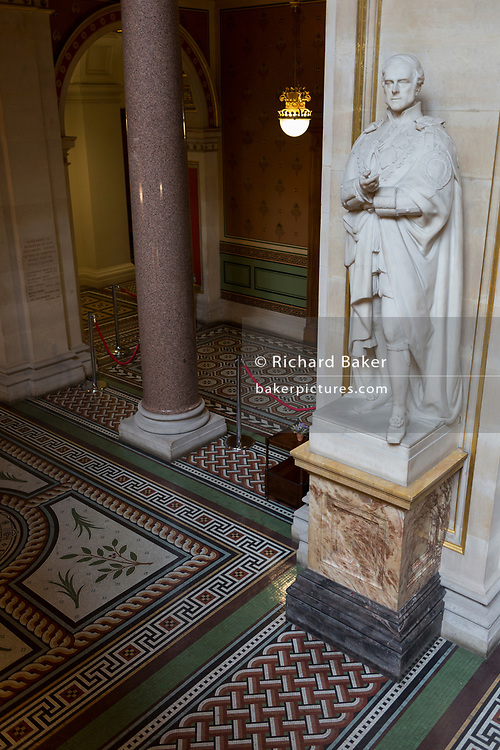 The statue of the 4th Earl of Clarendon KG GCB at the foot of the Grand Staircase in the Foreign and Commonwealth Office (FCO), on 17th September 2017, in Whitehall, London, England. George William Frederick Villiers, 4th Earl of Clarendon KG GCB PC (1800–1870), was an English diplomat and statesman. The main Foreign Office building is in King Charles Street, and was built by George Gilbert Scott in partnership with Matthew Digby Wyatt and completed in 1868 as part of the new block of government offices which included the India Office and later (1875) the Colonial and Home Offices. George Gilbert Scott was responsible for the overall classical design of these offices but he had an amicable partnership with Wyatt, the India Office's Surveyor, who designed and built the interior of the India Office.