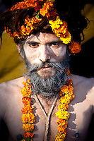 naga baba, or sadhu with white face and flowers in hair attends kumbh mela festival in india
