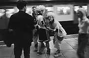 Football fans on a tube platform wearing wigs and face paint