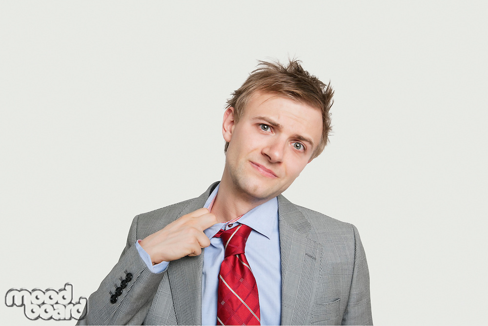 Portrait of young businessman loosening tie over colored background