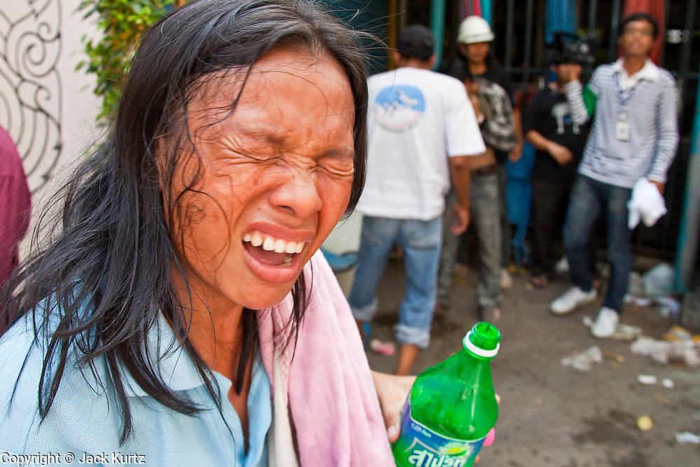 14 MAY 2010 - BANGKOK, THAILAND: A woman reacts to being tear gassed by Thai troop on Rama IV Road in Bangkok Friday afternoon. Thai troops and anti government protesters clashed on Rama IV Road Friday afternoon in a series of running battles. Troops fired into the air and at protesters after protesters attacked the troops with rocket and small homemade explosives. Unlike similar confrontations in Bangkok, these protesters were not Red Shirts. Most of the protesters were residents of nearby Khlong Toei slum area, Bangkok's largest slum area. The running battle went on for at least two hours.   PHOTO BY JACK KURTZ
