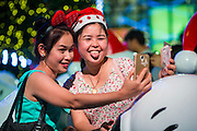 "17 DECEMBER 2014 - BANGKOK, THAILAND: Women pose for ""selfies"" among the Christmas decorations in front of Central World in Bangkok. Thailand is overwhelmingly Buddhist. Christmas is not a legal holiday in Thailand, but Christmas has become an important commercial holiday in Thailand, especially in Bangkok and communities with a large expatriate population.    PHOTO BY JACK KURTZ"