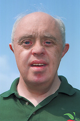 Portrait of man with Downs Syndrome working on community allotment project,