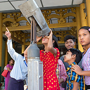 Myanmar (Burma). Yangon. Shwedagon pagoda . Visitors use a telescope to look at the umbrella (hti) on the top....the finial ornament that tops almost all Burmese pagodas.