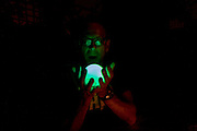 A man holds a glowing orb in spread fingers that shines up into his face and glasses.
