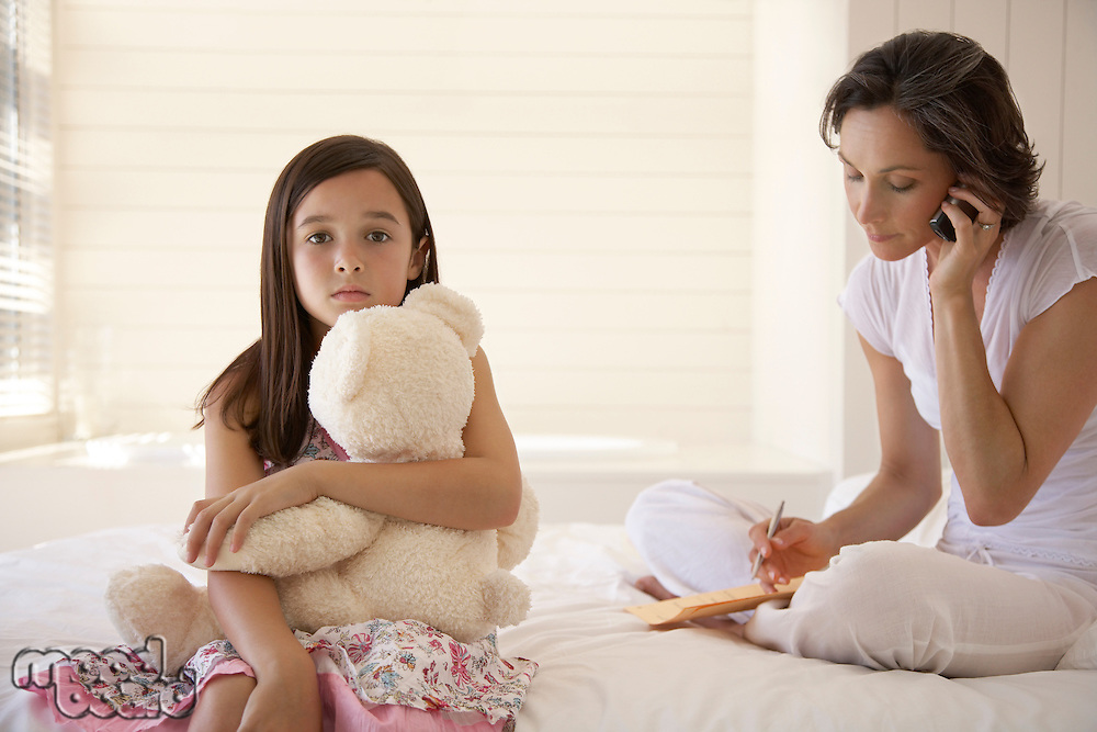 Mother using cell phone daughter cuddling teddy sitting on bed