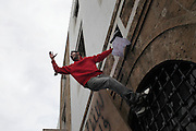 A Tunisian climbs a wall of the governement building during a demonstration demanding the dissolution of the new interim governement.